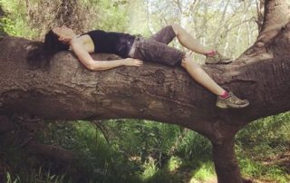 Jules Swales in nature laying on a tree branch looking up and thinking creatively